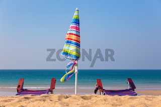 Colorful beach umbrella with chairs on beach