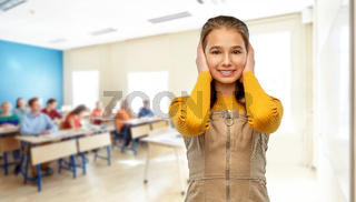 student girl closing ears by hands at school