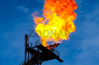 Burning torch at the torch plant burning associated natural gas on the oil platform