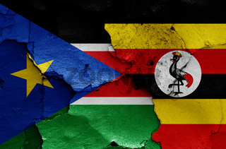 flags of South Sudan and Uganda painted on cracked wall