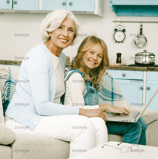 Grandmother happy to help her granddaughter with laptop