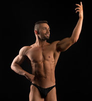 Handsome muscular athlete view in dark room
