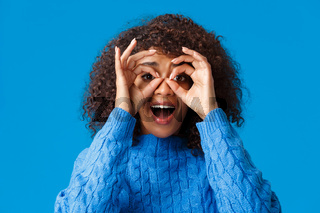 Surprised and fascinated, excited african-american woman looking through circles okay gesture like holding binocular and checking out impressed awesome promo, smiling amused