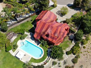 Aerial view of residential villa covered with a red tent while being fumigated for termites.