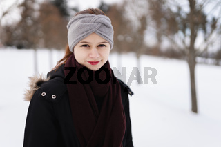 Happy young girl in winter clothes with snow looking in the camera