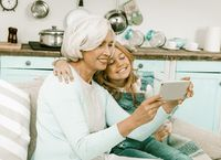 Grandmother and granddaughter happily making selfie or family photos