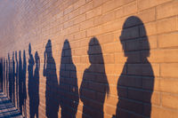 People crowd shadows lined up against a red brick wall. They are in a queue for changes in life. Social distance, covid and immigration issue concept