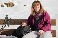 Frau macht Pause auf einer Bank im Winter