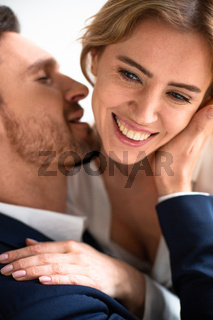 Happy passionate couple in love touching, kissing and huging. Focus on female happy eyes and hand in foreground. Enjoyment concept. Close up shot