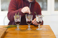 Man decorating elegant wineglasses with herbs