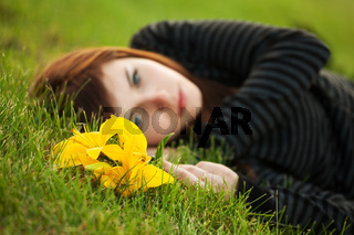 Sad young woman with a flowers lying on the grass