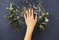 Female hand with manicure over table with plants and confetti