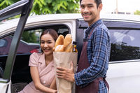 Asian woman take delivery grocery bag from Drive Thru supermarket