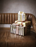 Stack of Christmas gifts on sofa