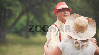 Elderly Man And Woman Dancing In The Garden