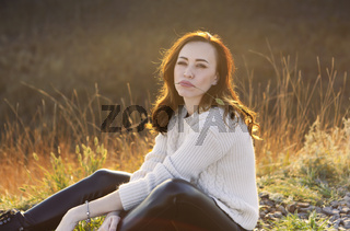 Young woman sitting in high grass at sunset