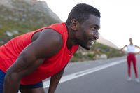 Fit african american man in sportswear standing and resting on a coastal road