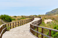 Wooden empty board walk leading through sandy dunes to Mediterranean Sea and beach of Los Arenales del Sol or Arenals del Sol. Costa Blanca, Europe, Spain. Espana