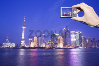 Tourist photographing the Pudong skyline at dusk