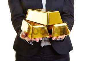 Hände halten Gold als Goldbarren