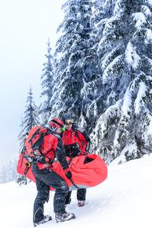 Ski patrol carry injured person in stretcher