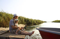 Man with kid fishing at river