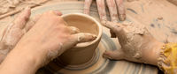 Beginner and teacher hands in clay at process of making crockery on pottery wheel