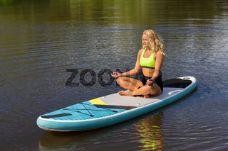 Young blonde woman meditating on SUP in water