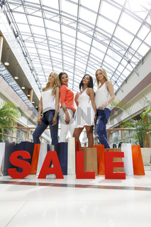 Female friends hold word SALE
