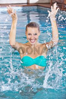 Frau im Schwimmbad spritzt mit Wasser