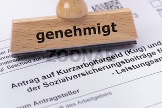Antrag auf Kurzarbeitergeld mit Holzstempel und Aufschrift genehmigt