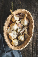 White garlic bulbs in basket on old wooden table and napkin.