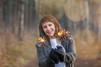 Smiling happy pretty woman enjoying bengal light among winter forest