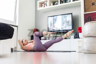 Attractive sporty woman working out at home, doing pilates exercise in front of television in her small studio appartment. Social distancing. Stay healthy and stay at home during corona virus pandemic