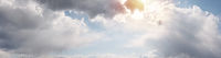 Beautiful cloudscape with warm sunny tonings. Blue sky covered with clouds. Warm sunlight and sun rays pass through the clouds and illuminate them. Ultra-wide panoramic natural background