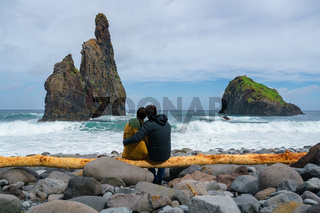 Janela Islets in Porto Moniz in Madeira with a couple sitted on a yellow tree on the ground