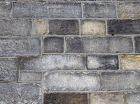 a full frame image of a large old dark stone wall made of large irregular sandstone blocks