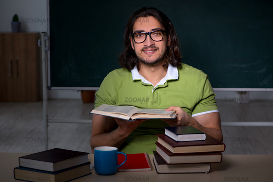 Young male student preparing for exams in the classroom