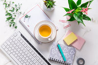 Flat lay home business desk with communication device with cup of tea and writing tools. Feminine business mockup
