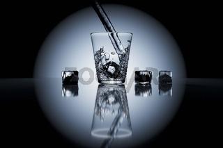 Graustufen Standbild von Wasser, was in ein Glas geschenkt wird und mit Eiswürfeln