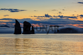 Three Brothers Rocks in Pacific Ocean at sunset. Kamchatka Peninsula, Russian Far East