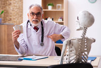Old male doctor and skeleton patient in the clinic
