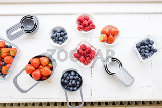 Strawberries, blueberries, and raspberries in plastic containers from above