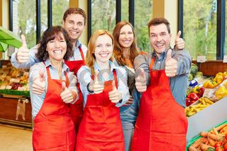 Team im Supermarkt hält Daumen hoch