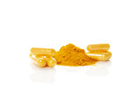 Turmeric (curcumin) powder heap and capsules isolated on white.
