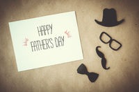 Father's day greeting card. White card with decorative elements on craft paper background.