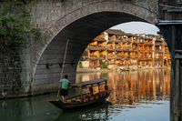 Man on old wooden boat in Fenghuang