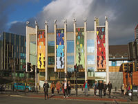 people crossing the road in front of the brightly coloured facade of the new west yorkshire playhouse theatre building in saint peters street Leeds.