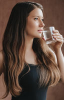 Woman drinking water out of glass at home, stay healthy and hydrated, diet and wellness