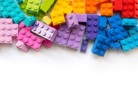 A lot of Colorful Plastick constructor blocks on white background. Popular toys. Copyspace